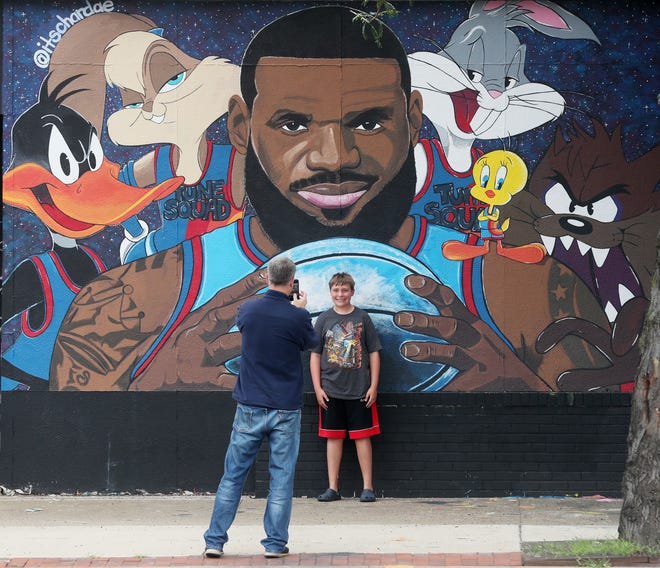 """Mike Plybon of Norton takes a photo of his son Austin, 14, with the LeBron James """"Space Jam"""" mural on West Market and North Valley Street on Wednesday July 21, 2021."""