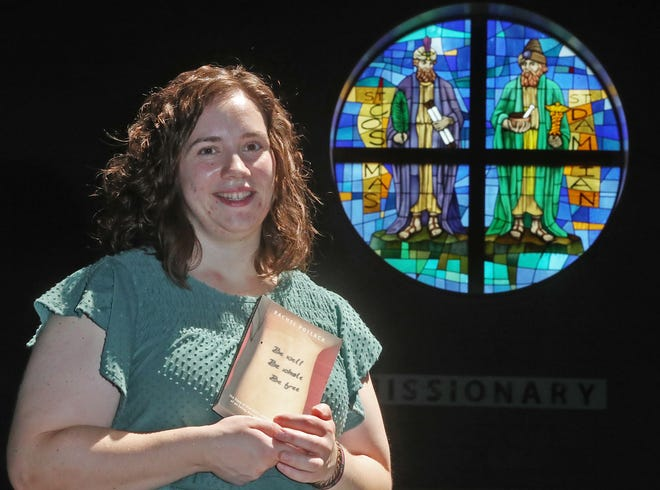 """Rachel Pollack, 30, of Twinsburg, holds her book, """"Be Well, Be Whole, Be Free: The Story of One Girl's Journey from the Darkness of an Eating Disorder to the Light of Recovery"""" in the sanctuary of Sts. Cosmas and Damian church, where she works."""