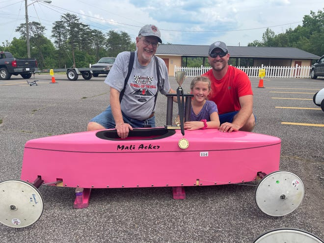 Richard Harvey Acker, from left, his granddaughter Amalia Acker and son Richard Gerald Acker show Amalia's trophy and car after competing in a rally in Charleston, W.Va.
