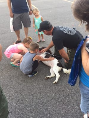 Cuyahoga Falls Police officer Ed Dennis invites children to visit with police K-9 DanC, at a past National Night Out event. Falls police will host a National Night Out program in a portion of the Natatorium parking lot from 5:30-7:30 p.m. on Aug. 3.
