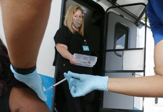 Nurse Kim Drury  watches as Nurse Manager Ashley Chaney vaccinates Ebony Smith on Thursday at the Summa Mobile Health Unit during an OPEN M community event in Akron.