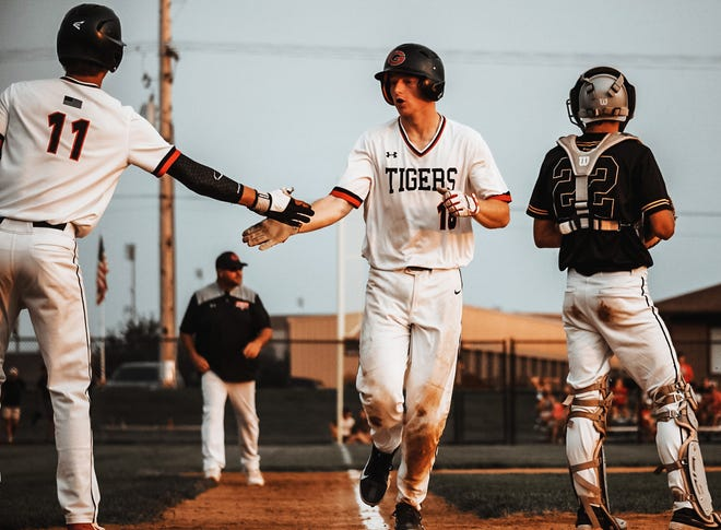 Gilbert's Nick Chasey receives a high-five from teammate Jacob Papesh during the Tigers' Class 4A substate final loss to Winterset Wednesday at the Gilbert Middle School Baseball Field in Gilbert. The Tigers suffered a 4-2 loss in eight innings to come up just short of returning to state.