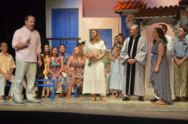 """Future plans for several characters change after Donna Sheridan (at right, played by Billie Harvey) finally reveals her secret during the wedding of her daughter, Sophie Sheridan (in wedding gown, played by Emily Borbon), in the Lyric Theatre's production of """"Mamma Mia!"""" The show wraps up its final weekend with performances at 2:30 p.m. Friday, 7:30 p.m. Saturday, and 2:30 p.m. Sunday. Also pictured in the foreground are Sam Carmichael (left, played by Jonathan Harvey), and Father Alexandrios (played by Doug House)."""