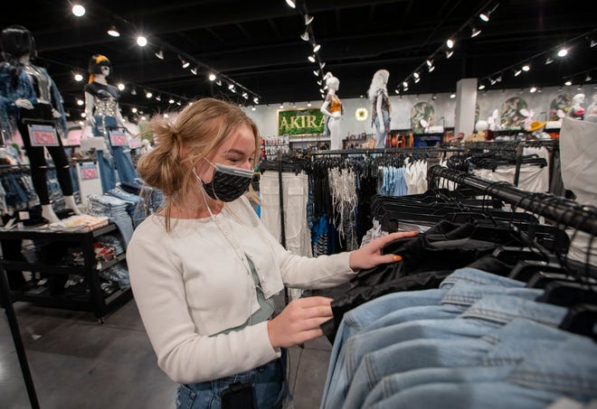 Store manager Ashley Ellington straightens racks of women's clothing, footwear, and accessories at Akira in Polaris Fashion Place.