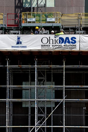 Construction workers can be seen above the scaffolding Thursday at the Rhodes State Office Tower,a 41-story, 629-foot skyscraper located on East Broad Street on Capitol Square in downtown Columbus.  Workers are beginning to remove scaffolding from the tower that was erected during renovation work to the structure, which opened in 1974.