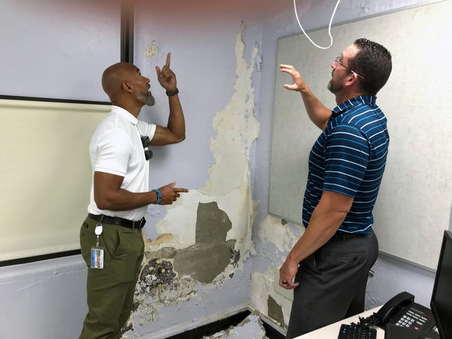 Reynoldsburg City Schools Superintendent Melvin Brown (left) and district business director Chris Reed look at severe water damage on the third floor of Hannah Ashton Middle School, 1482 Jackson St. Parts of the building date to 1868, and its construction lets water leak inside on all three floors, Reed said. Brown said the water damage shown here occurred after the school year ended May 27.