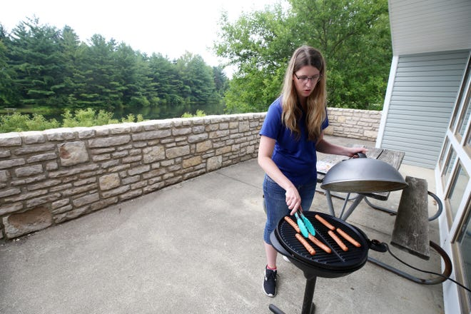 Bethany Dresback, an administrative professional with the Ohio Department of Natural Resources, grills hotdogs on the patio of the newly renovated Alum Creek State Park park office July 21, which was National Hotdog Day. The park's operations were moved to the newly renovated office at 3615 S. Old State Road in Delaware. The new office is open 8 a.m. to 4:30 p.m. Mondays through Fridays for watercraft registrations, boat inspections and general park visitor information.