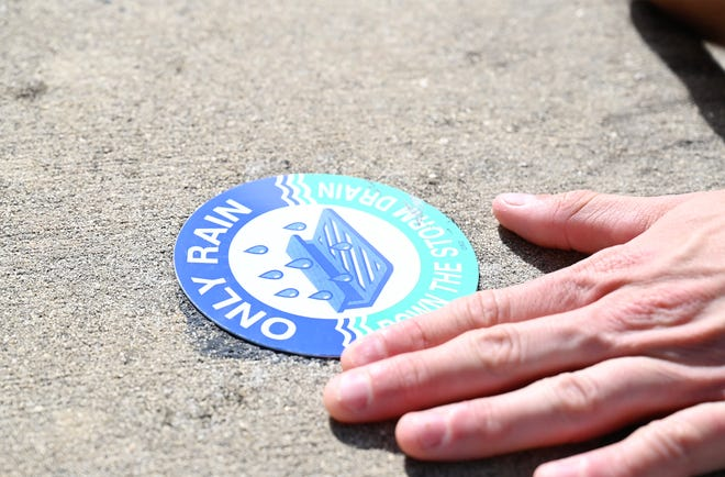 """Volunteers with Keep Lake Beautiful help bring awareness to storm drains by marking them with a sign that reads """"only rain down the storm drain."""" [Cindy Peterson/Correspondent]"""