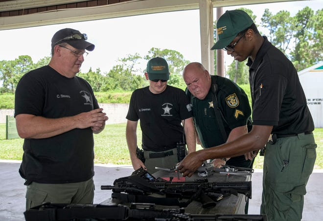 From left, Lake County Sheriff's Sgt. Chris Stevens, Dep, Matthew Drennan, Corp. Jack Frost  and Dep. Cameron Robinson peer over a damaged drone during a training session at the Lake Technical College Institute of Public Safety weapons and driving range in Tavares on Wednesday, July 21, 2021. [PAUL RYAN / CORRESPONDENT]