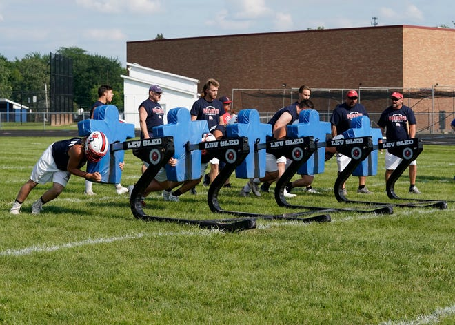 Britton Deerfield linemen push the sled during Wednesday's Lenawee County Lineman Challenge at Adrian High School.