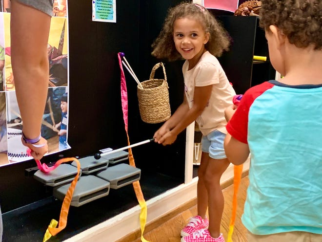 Mae Edwards plays on tonal blocks, one of many instruments featured as part of aMuse'um Children's Museum's latest Asian culture exhibit.