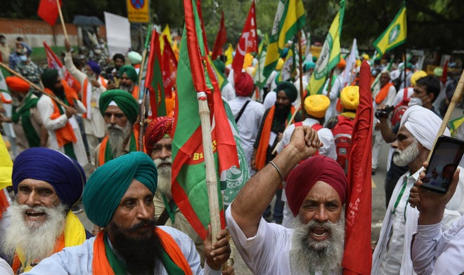 Farmers shout anti-government slogans during a protest in New Delhi, India, Thursday, July 22, 2021. More than 200 farmers on Thursday began a protest near India's Parliament to mark eight months of their agitation against new agricultural laws that they say will devastate their income.