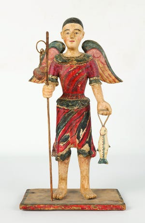 The 13-inch-high antique wooden San Rafael figure holding a staff and a fish sold at a Cottone auction for $9,600.