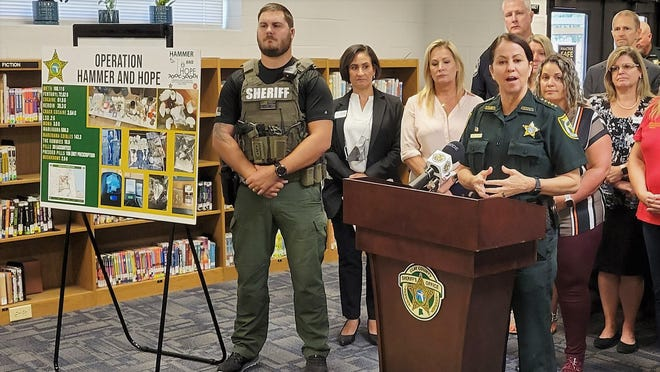 Clay County Sheriff Michelle Cook (at podium) details the arrests and drug seizures from Operation Hammer and Hope on Thursday. She is flanked by county officials and caregivers who will join the department in a community anti-drug event Friday at Wilkinson Elementary School in Middleburg.