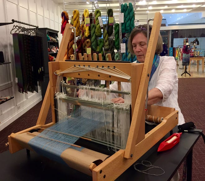 Mary Buschhorn weaves yarn at the Fiber Arts Store in Bloomington's College Mall.
