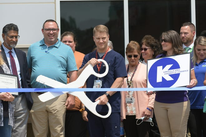 Dr. Kelly Burchett, center, poses during a ribbon-cutting ceremony on Thursday, July 22, in front of Complete Family Medicine's Specialty Group.