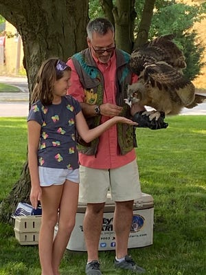 Library program participant Grace, left, feeds Annie the Owl during Thursday's Silly Safaris show. The program, a live interactive animal conservation education program, was held on the lawn of the Carnegie building in Lincoln.