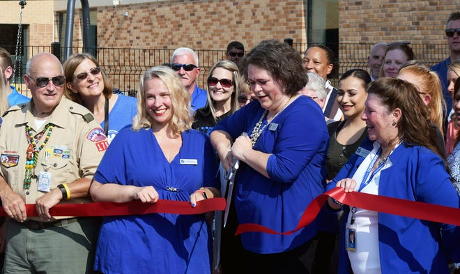 Leavenworth Board of Education President Judi Price cuts a ribbon Wednesday in celebration of the opening of the Earl Lawson Early Education Center. Price was surrounded by fellow board members and other representatives of the Leavenworth public schools.