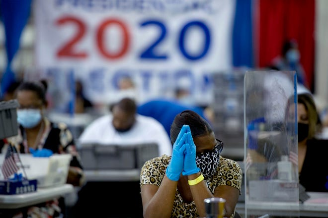 Palm Beach County Supervisor of Elections employees work among COVID-19 safety barriers at the Supervisor of Elections Voting Equipment Service Center in Riviera Beach on Nov. 3. MEGHAN MCCARTHY/Palm Beach Daily News
