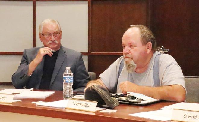 Fairbury Alderman Jon Kinate, left, listens as Alderman Charlie Hoselton speaks during Wednesday's Fairbury City Council meeting.