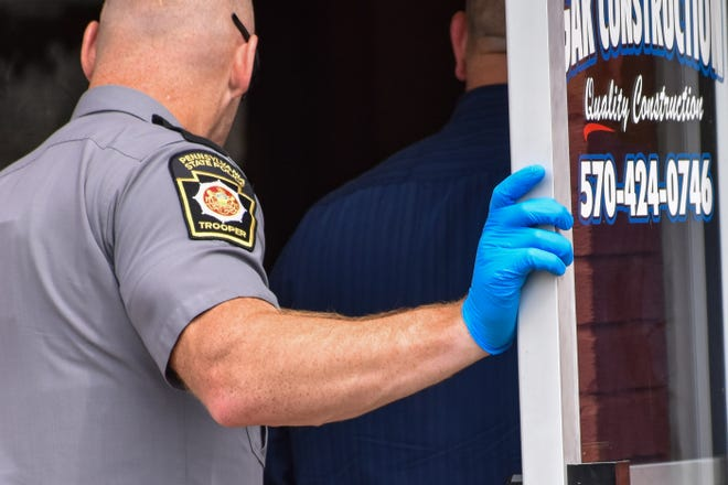 A Pennsylvania State Police trooper walks into the building on Washington Street in East Stroudsburg next to the lot where a woman's body was found in a dumpster on Thursday, July 22, 2021.