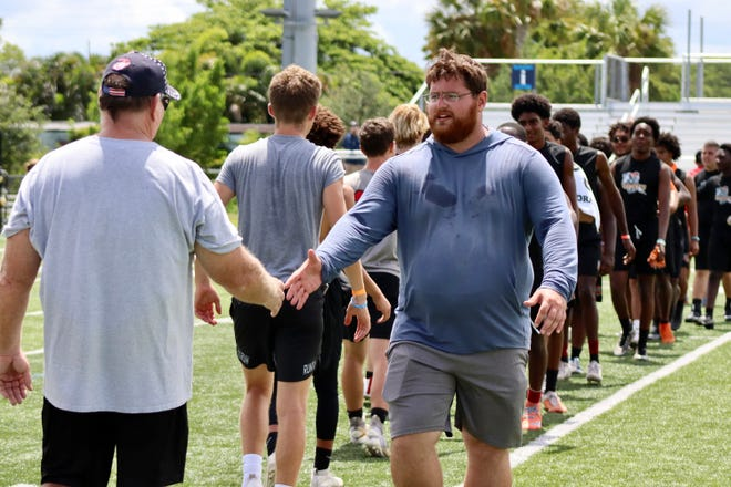 John I. Leonard head coach Austin Van Es shakes hands with the players and coaches of St. Andrew's after a victory in a summer 7-on-7 tournament.