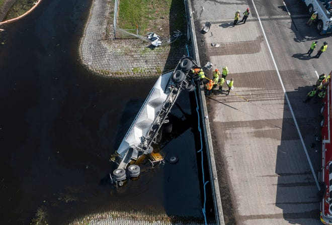 A tractor trailer in a canal on the Florida Turnpike after a crash at mile marker 84 between Boynton Beach Boulevard and Atlantic Avenue in Palm Beach County, Florida on July 22, 2021. (GREG LOVETT/PALM BEACH POST)
