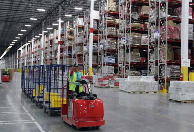This image taken in March 2017, when Amazon's Fall River fulfillment center opened, shows the expanse of the processing center as a worker drives items through it.