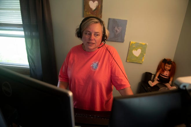 Although she recently went to work in an office, Marti Loughney worked from home in Mogadore for her Kent State University position. Loughney had dual computer screens set up, used a head piece microphone and a desk modified for both standing and sitting positions. Her office, which is also a bedroom, is decorated with items from her previous office outside of the home and items, such as the doll, a gift from her daughter, Katie, to keep her company during work hours.