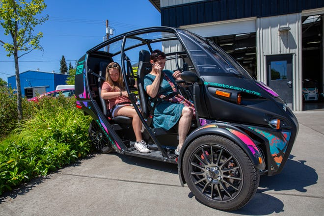 From left, Orrin Offchiss and her grandmother, Cindi Palman, strap into a rental Arcimoto FUV, or Fun Utility Vehicle on Friday. Arcimoto, a company making electric vehicles based in Eugene has begun renting out their fleets in multiple cities in the United States and producing vehicles for customers worldwide.