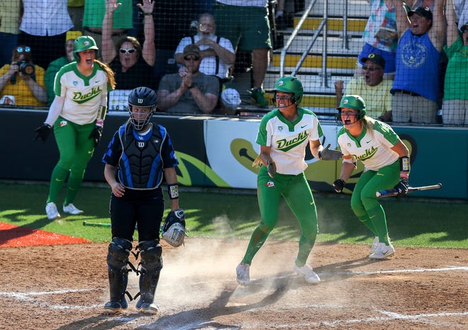 Oregon's Nikki Udria, second from right, celebrates after scoring on a Mia Camuso double in the seventh inning of a May 27, 2017, NCAA Super Regional win over Kentucky as Gwen Svekis, left, and Miranda Elish, right celebrate the victory. (Collin Andrew/The Register-Guard)