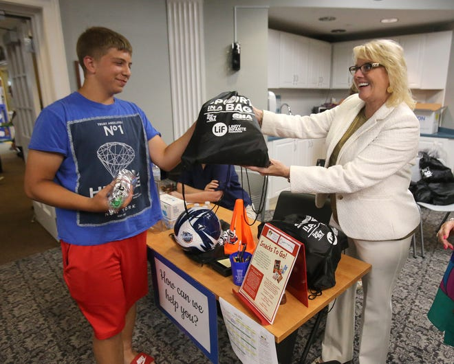 """Dominic Stahlman receives his sports bag from Massillon Mayor Kathy Catazaro-Perry on Thursday at the Massillon Public Library during the """"Snacks to Go"""" and """"Sport in a Bag"""" program."""