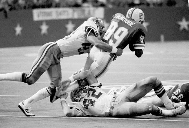 Dallas safety Cliff Harris (left) tackles Miami receiver Nat Moore as Cowboys safety Randy Hughes (42) struggles to grab Moore's legs at Irving, Tex., Aug. 20, 1977. (AP Photo/Pete Leabo)