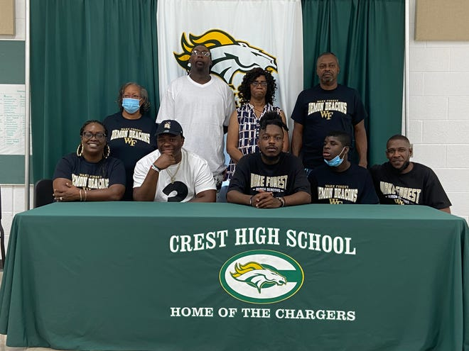 Crest's Eli Hall (seated, second from left) takes photos with family members after verbally committing to play football at Wake Forest.