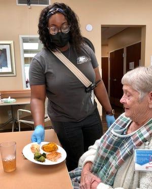Keairah Dawkins serves lunch to Helen Barnett at the Life Enrichment Center in Shelby.
