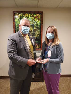 Kelsey Moran, a certified nursing assistant at War Memorial Hospital, being presented with the award by CEO and president of War Memorial Hospital, David Jahn.