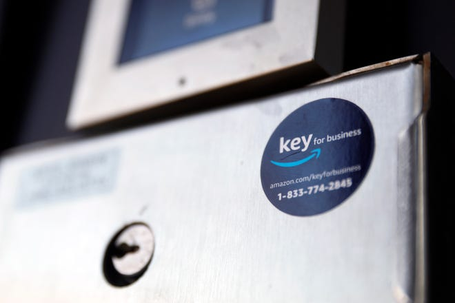 A blue sticker with the Amazon logo is displayed on a buzzer system in the apartment building of Jason Goldberg, chief commerce strategy officer at marketing company Publicis Communications, Monday, March 29, 2021, in Chicago. Amazon is making a push to install a device on buzzer systems in apartment buildings throughout the country that allows its delivery drivers to whip out a phone, tap a button and unlock a building's front doors whenever they need to leave packages in the lobby instead of the street. (AP Photo/Shafkat Anowar)