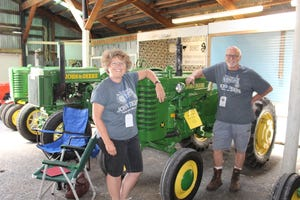 Chris and Frankie Lease of Wellersburg brought their 10 John Deere tractors to the Maple City Classic Tractor Roundup at the Somerset County Fairgrounds in Meyersdale over the weekend. Their entries were among 89 tractors on display for the three-day event. Here, they stand by a tractor once owned by Chris's father, the late Raymond Lepley, an original 1948 John Deere M that they were able to buy back into the family.