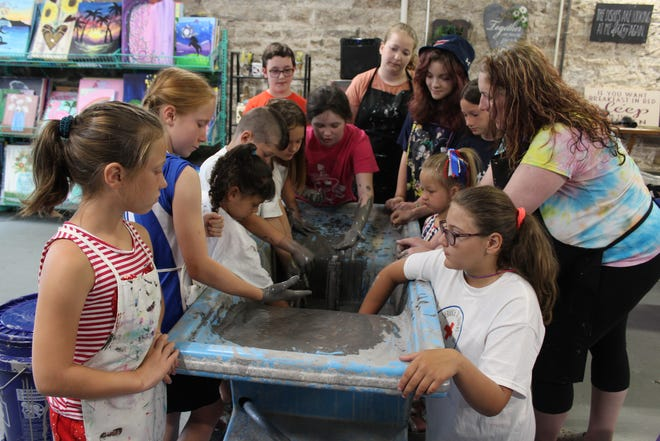 Students (from left): Macey Moon, Anna Moon, Kinzlee Waugh, Jacob Waugh Jr., Autumn Randolph, Amber Turner, Heath Miller, Kaleigh Vinzani, Tarrah Cox, Lia Fairman, Harper Randolph and Kalli Kimble stand around Jessica Cook (far right), new owner of the Uptown Painting Party in Somerset, during a lesson on ceramic making during summer camp. The children all reach in the pouring table and feel the slip that will be used to make their very own ceramics. It is on this day, the children will learn the long process of making a ceramic and after their cast is released and dried, they will then learn how to clean them and fire them and eventually paint their creations. This is just one of the fun things the students have been learning during their 10-course summer camp at Uptown Painting Party. Students Delilah Morris and Danica Morris are absent from the photo.