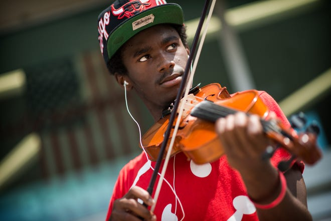Dextorist Timmons plays the violin Tuesday, Aug. 12, 2014, in front of Walgreens on Ramsey Street.