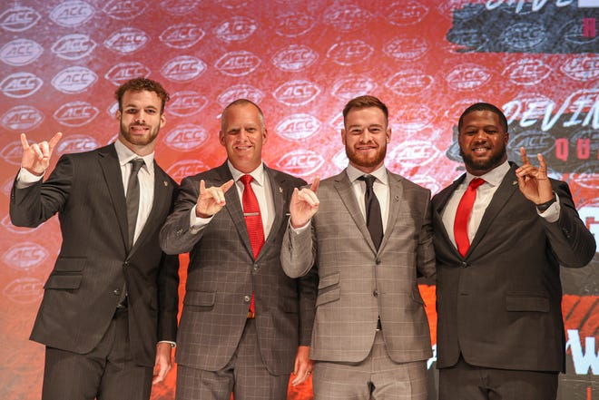 North Carolina State linebacker Payton Wilson, from left, coach Dave Doeren, quarterback Devin Leary and center Grant Gibson pose for a photo during an NCAA college football news conference at the Atlantic Coast Conference media days in Charlotte, N.C., Thursday, July 22, 2021. (AP Photo/Nell Redmond)