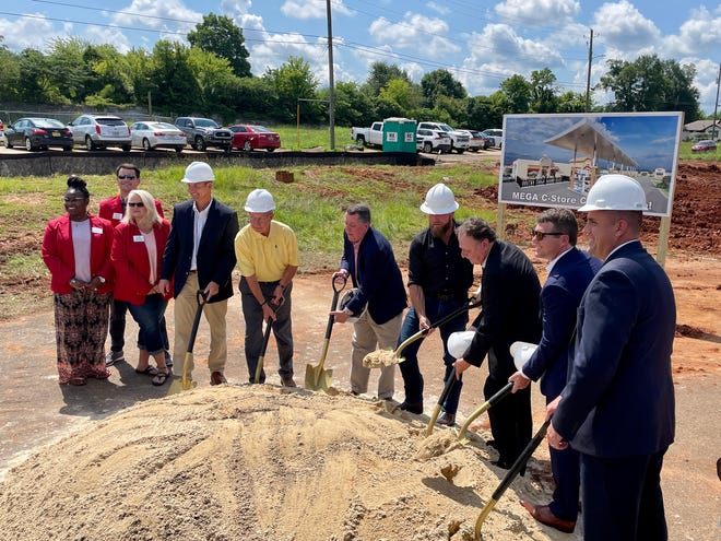 Ambassadors from the Chamber of Commerce of West Alabama, in red, are joined by city staff members, elected officials and the developers of a new ExtraMile convenience store in Alberta for a groundbreaking ceremony to commemorate the gas station's construction. [Staff photo/Jason Morton]