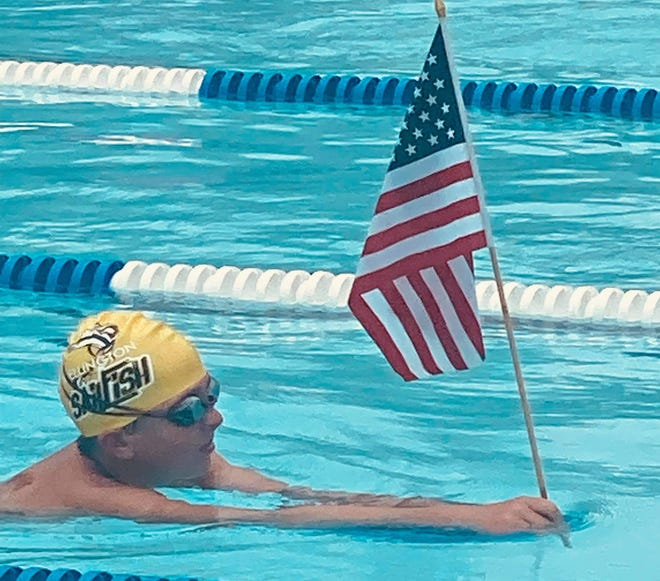 Wellington Sailfish swimmer holding the American flag in the pool at districts.