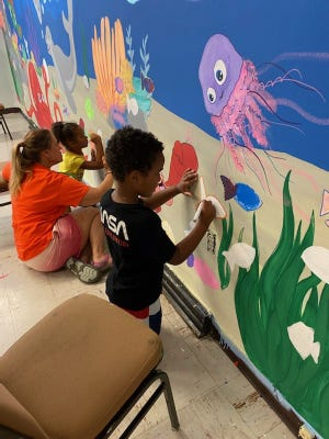 From left, Jenna Light, Kerry Roberts and Demetrius Grinnon paint a mural for the kids preschool class during Vacation Bible School at Brookville Bible Church, Holbrook.