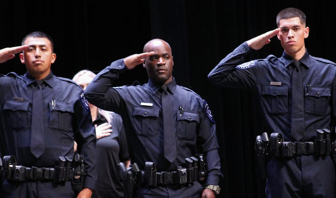 Cadets, from left, Arni Lopez, Eric Massey and Nicholas Silva salute during the singing of the national anthem to start Thursday's Class 58 graduation ceremony for the Abilene Police Department at the Abilene Convention Center.