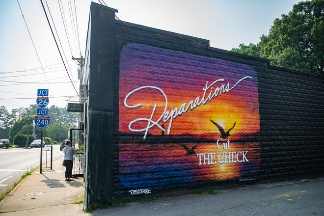 A pro-reparations mural painted on the side of Desoto Lounge on Haywood street by local muralist IanThePainter.