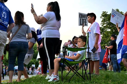 A child sits while being surrounded by supporters of President Joe Biden, and former President Donald Trump, on the corner of Delhi Road and Neeb Road outside of Mount Saint Joseph University, where President Biden is set to speak at a town hall on Thursday, July 21, 2021.