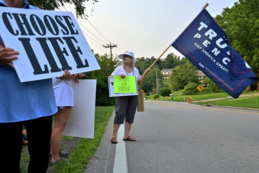 Ann Kissell, of Northside, shows her support for former President Donald Trump by protesting the arrival of President Biden on the corner of Delhi Road and Neeb Road outside of Mount Saint Joseph University, where Biden is set to speak at a town hall on Thursday, July 21, 2021.