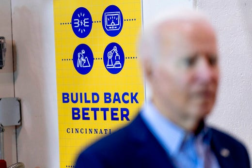 """A poster that says """"Build Back Better"""" is displayed on the wall behind President Joe Biden as he speaks with an instructor and an apprentice at the IBEW / NECA Electrical Training Center in Cincinnati, Wednesday, July 21, 2021. (AP Photo/Andrew Harnik)"""