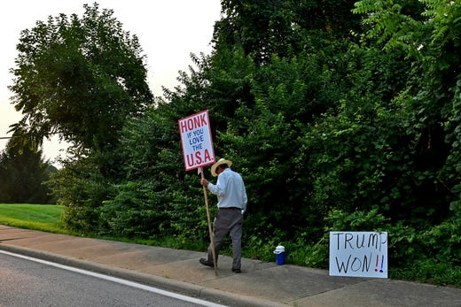 A supporter of former President Donald Trump takes a break from protesting the arrival of President Joe Biden on the corner of Delhi Road and Neeb Road outside of Mount Saint Joseph University, where Biden is set to speak at a town hall on Thursday, July 21, 2021.